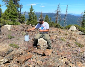 Brandon cleaning up old nails from the old fire lookout site with a magnet.